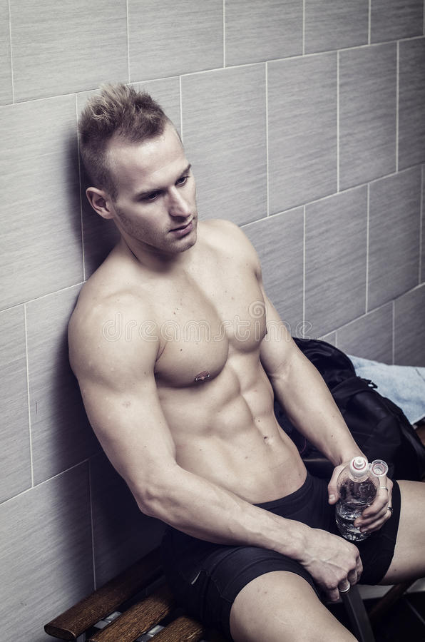 Blond shirtless athlete resting after workout. Blond shirtless young male athlete resting after workout, holding a water bottle and sitting against wall stock images