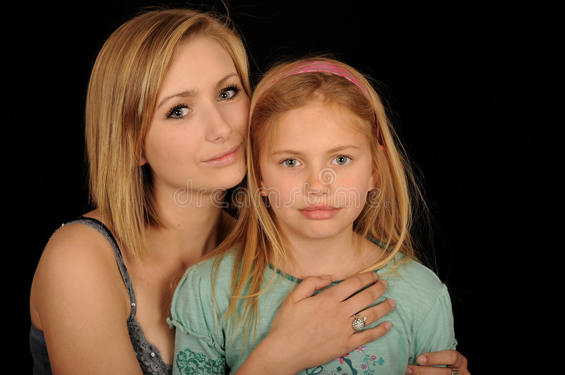 Blond sisters. Horizontal portrait of a teenage girl and her younger sister in an affectionate pose, isolated on a black background royalty free stock photography