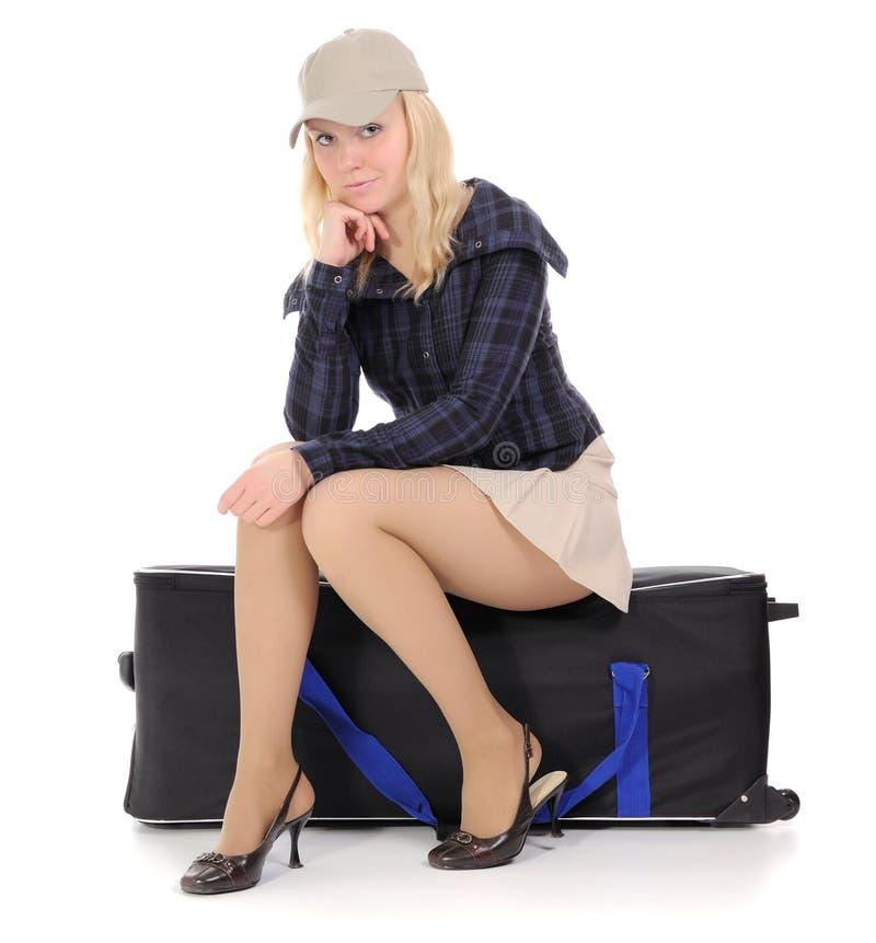 blond sittande resväska arkivfoto