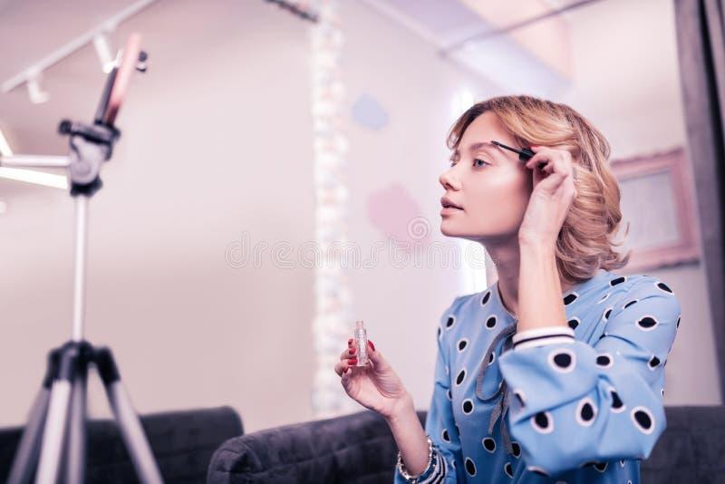 Blond skönhetblogger som använder för att stelna för krön, medan filma bloggen arkivfoto