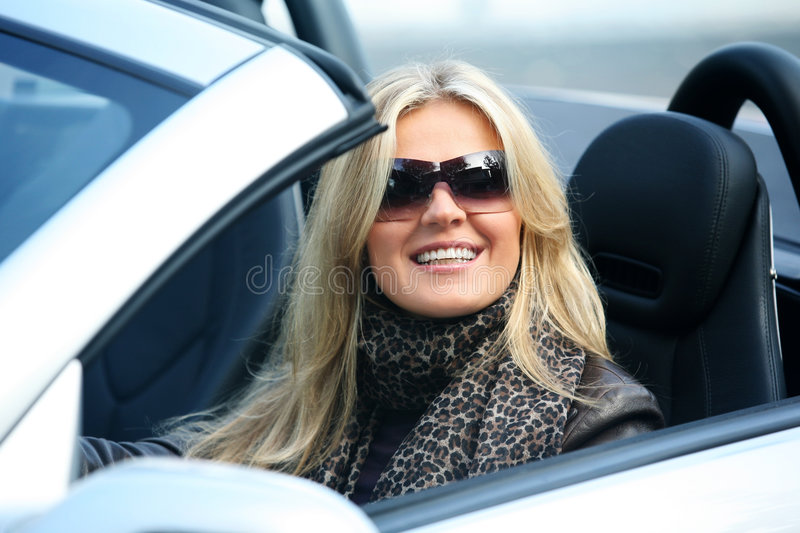 Blond smiling woman in a car royalty free stock photo