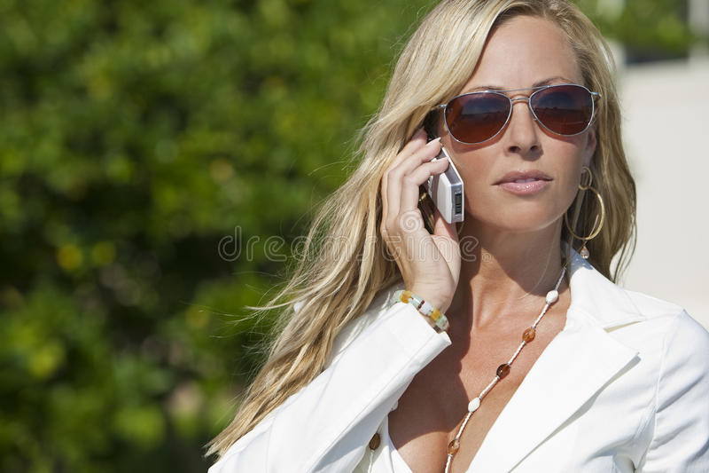 blond solglasögon för celltelefon som talar kvinnan royaltyfri fotografi