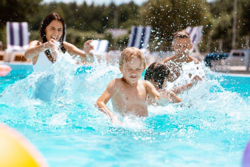 Blond sonkänsla som förbluffar simning med föräldrar och systern royaltyfria bilder