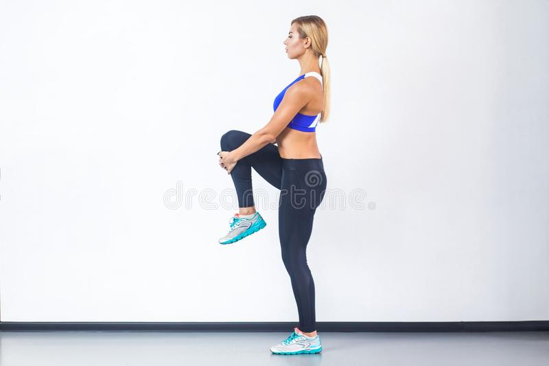 Blond sportig kvinna för Rofile sikt som balanserar på ett ben arkivfoton