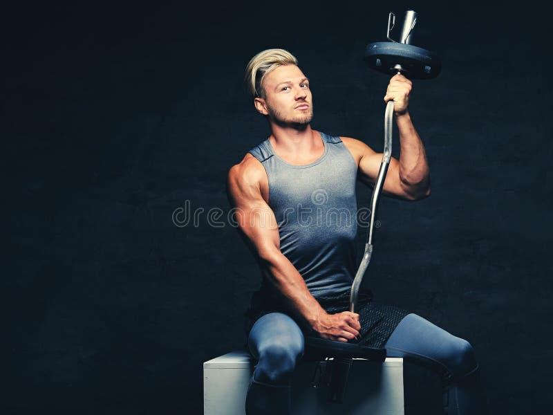 Blond, sportowa samiec, ubierał w popielatym sportswear trzyma barbel zdjęcie stock