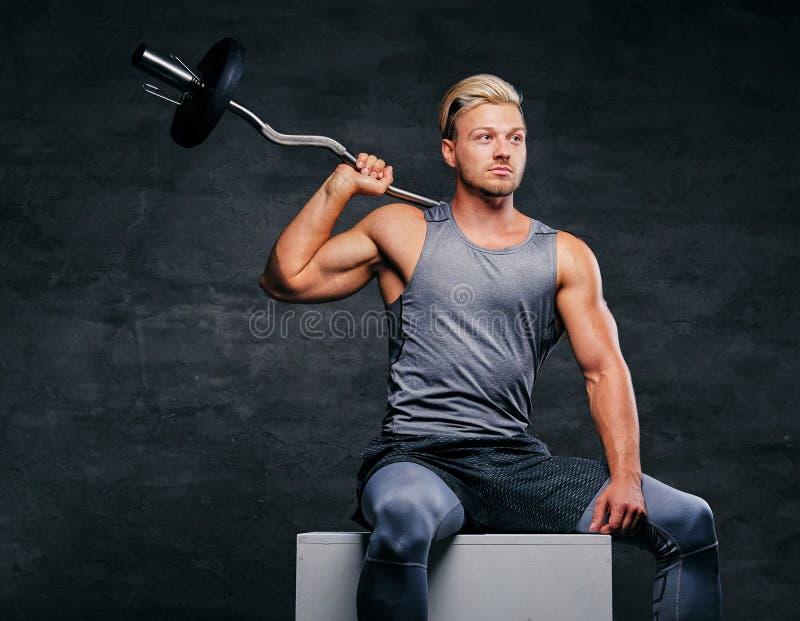 Blond, sportowa samiec, ubierał w popielatym sportswear trzyma barbel zdjęcia stock
