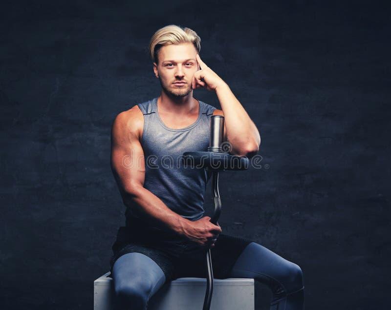 Blond, sportowa samiec, ubierał w popielatym sportswear trzyma barbel obraz royalty free