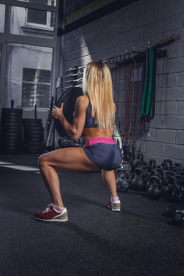 Blond sporty female from her back doing squats. stock photos