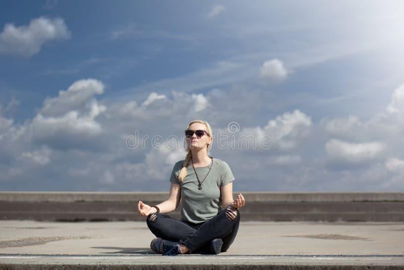 Blond stads- kvinna i mörk jeans och gymnastikskor som sitter i mitt av trottoar, tar ett avbrott och mediterar, med härlig bl royaltyfri bild