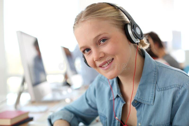 Blond studentkvinna i grupp med hörlurar arkivbilder