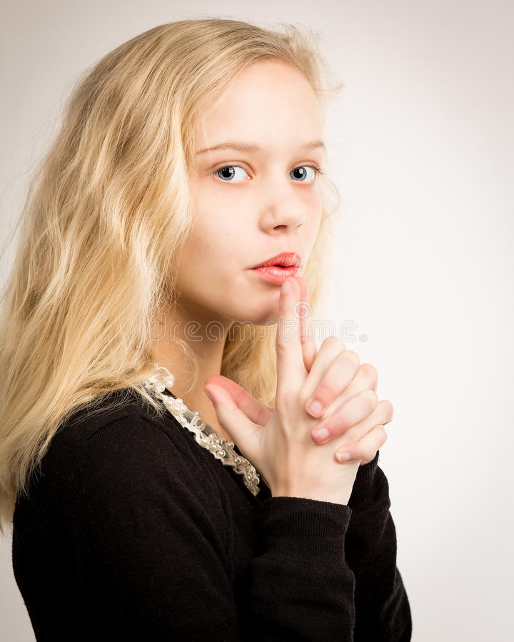 Blond Teen Girl Blowing Smoke From Finger Gun. Studio portrait of a beautiful blond teenage girl with long hair blowing imaginary smoke from the barrel of her stock image