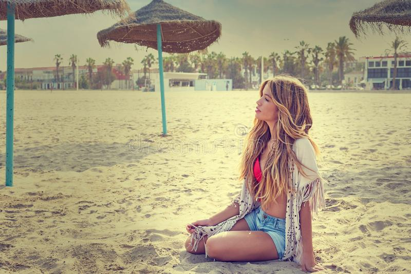Blond teen girl sit on the beach sand royalty free stock images