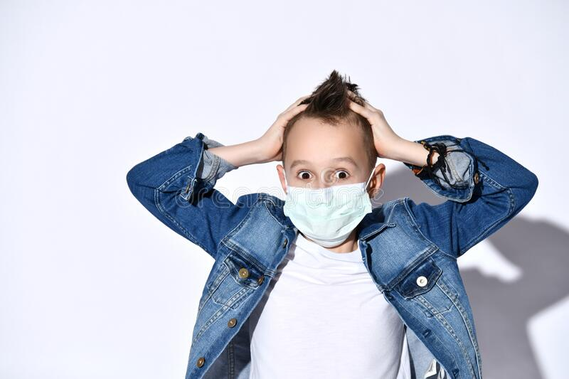 Blond teenage child in blue denim jacket, t-shirt. He in medical mask, clutching his head, posing isolated on white. Coronavirus. Blond teenage child in denim royalty free stock photography
