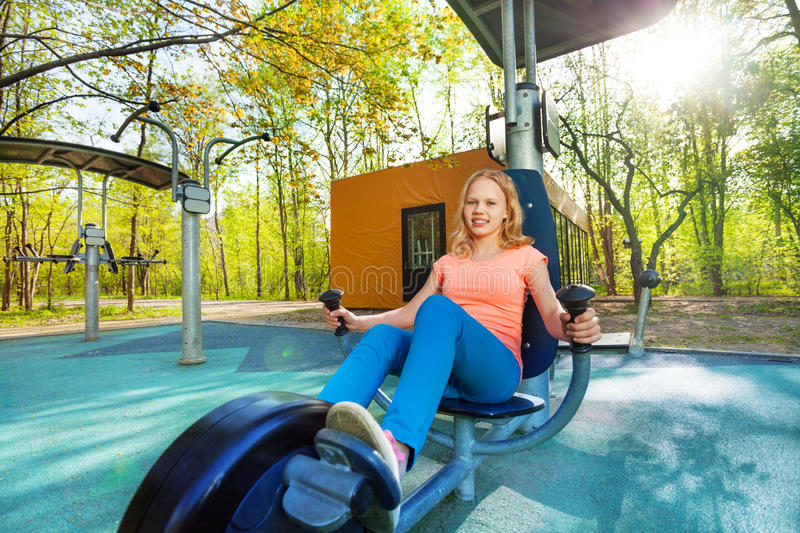 Blond teenage girl cycling on exercise equipment. Blond teenage girl cycling on the exercise equipment at the sports ground during summer day with trees on stock images