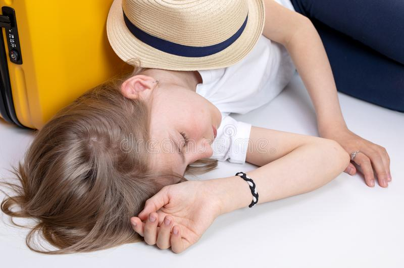 Blond teenage girl sleeping or resting near a yellow suitcase, a straw hat lies on it. Isolate on white stock image