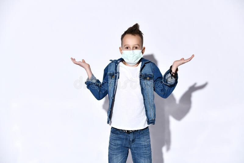 Blond teenage kid in blue jeans, jacket, t-shirt. He is in medical mask, looking confused, posing isolated on white. Coronavirus. Blond teenage kid in blue jeans stock image