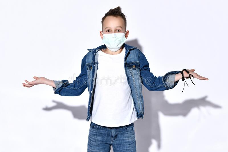 Blond teenage kid in blue jeans, jacket, t-shirt. He is in medical mask, looking confused, posing isolated on white. Coronavirus. Blond teenage kid in blue jeans stock photos
