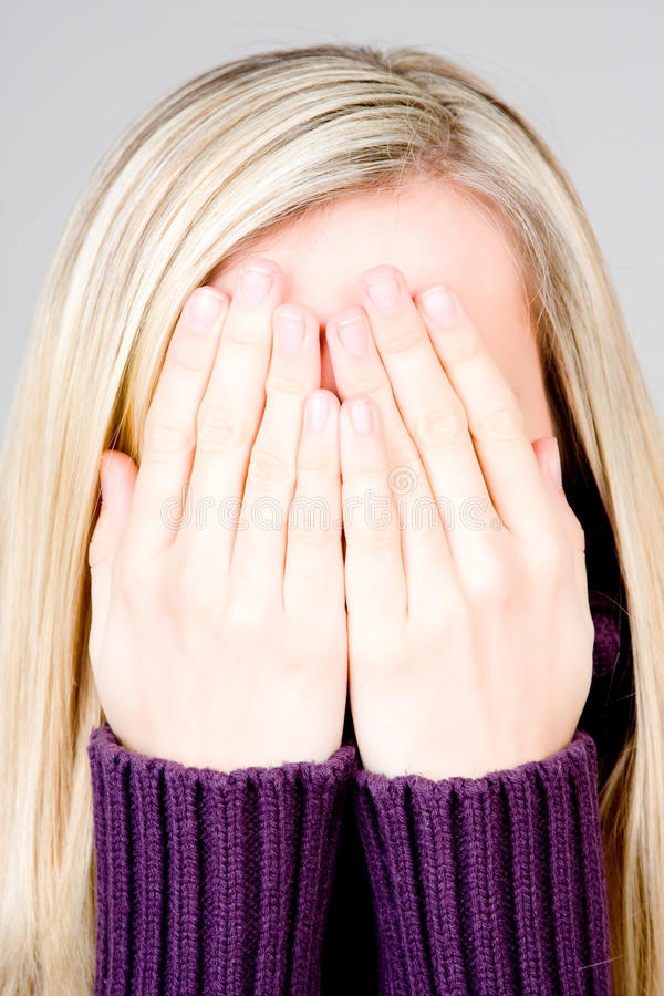 Blond teenager covering face. Portrait of blond haired teenager covering face with hands, studio background stock photo