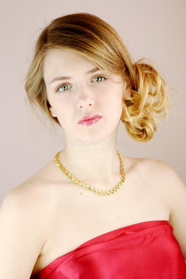 Blond tiener modelmeisje in rood satijn met gouden juwelenhalsband stock afbeeldingen