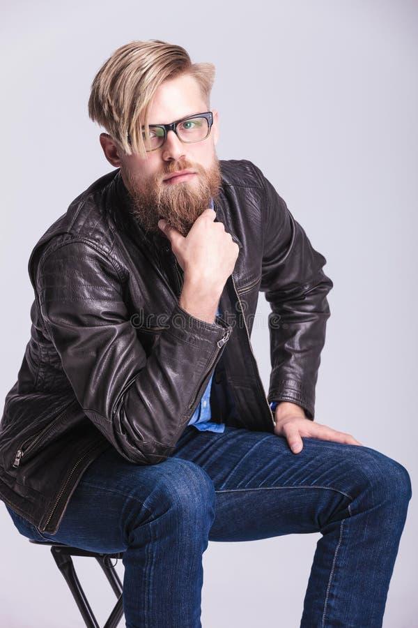 Blond tillfällig man som daltar hans långa skägg royaltyfria foton