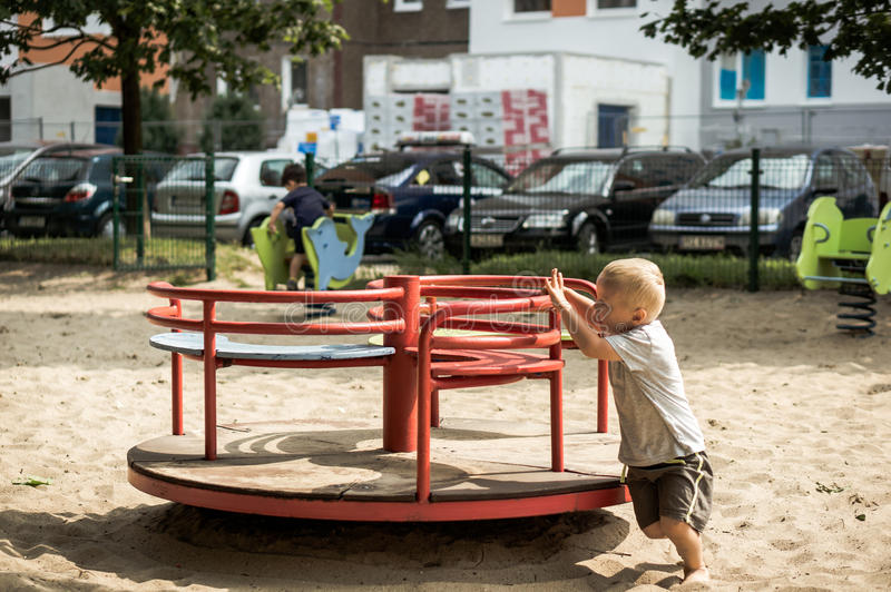 Boy pushing a roundabout stock photography