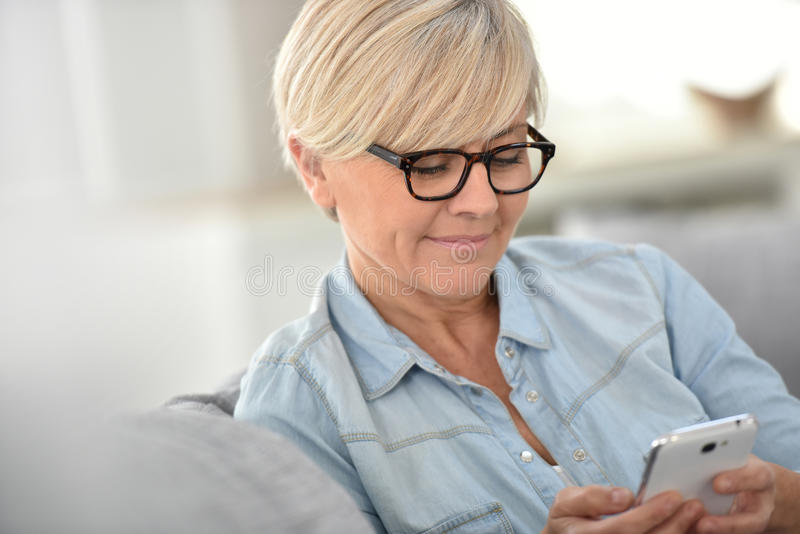 Blond trendy senior woman writing sms royalty free stock image