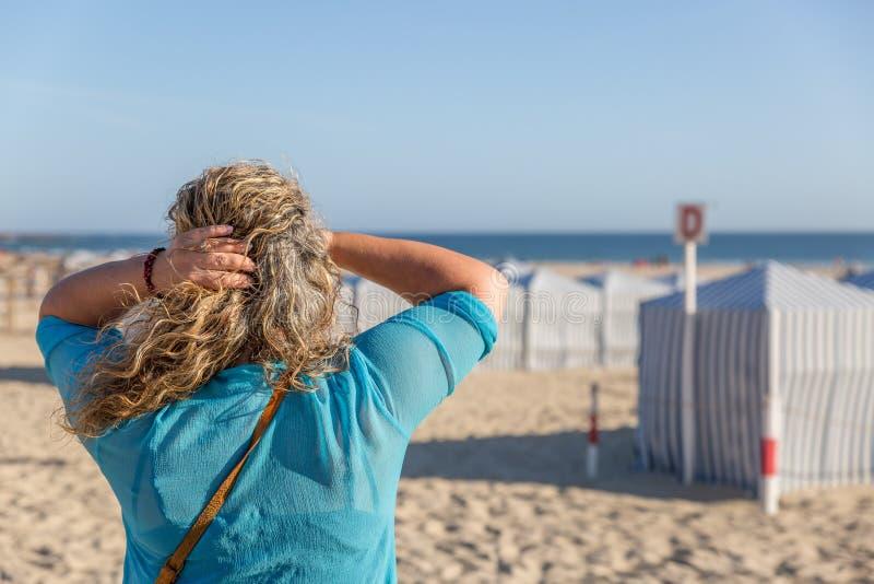 Blond turystyczna kobieta obserwuje horyzont podczas gdy na pięknej białej piasek plaży obrazy stock