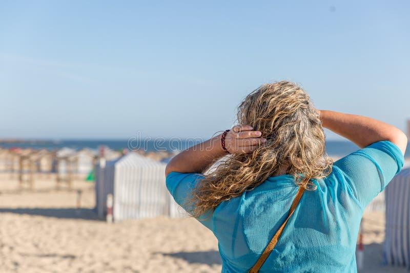 Blond turystyczna kobieta obserwuje placidly krajobraz, podczas gdy na pięknej białej piasek plaży na letnim dniu, zdjęcia royalty free