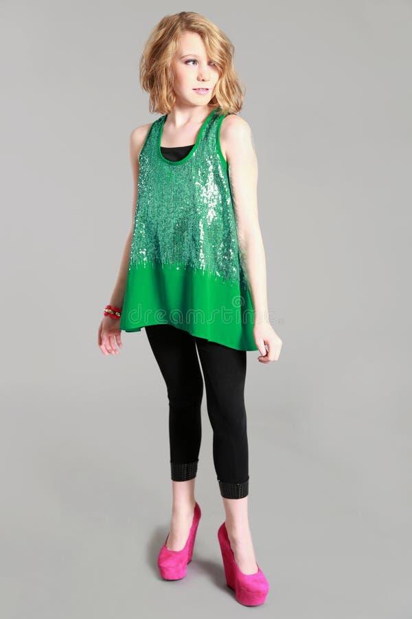 Blond tweenflicka i paljettgräsplanskjorta royaltyfri fotografi