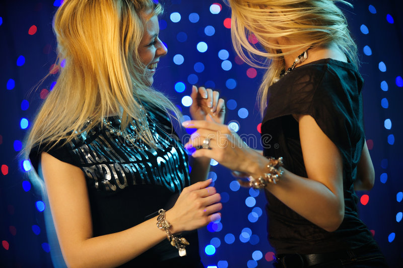 Blond twins dancing in the club. Horizontal image of blond twins dancing stock photography