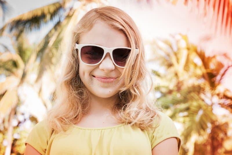 Blond uśmiechnięta nastolatek dziewczyna w okularach przeciwsłonecznych, stonowana fotografia obrazy stock