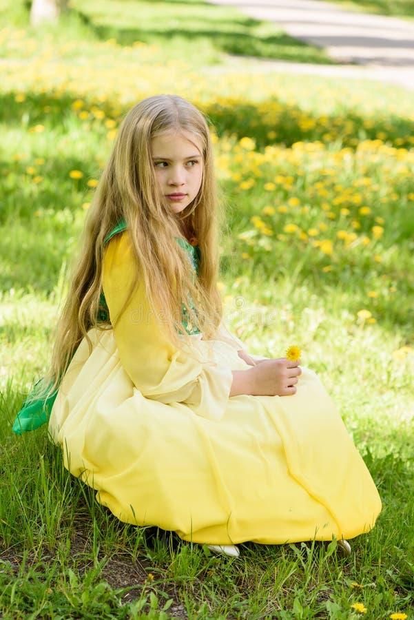 Blond ung flicka som poserar i en gul grön klänning som sitter på gräset med gula blommor för maskrosor royaltyfria foton
