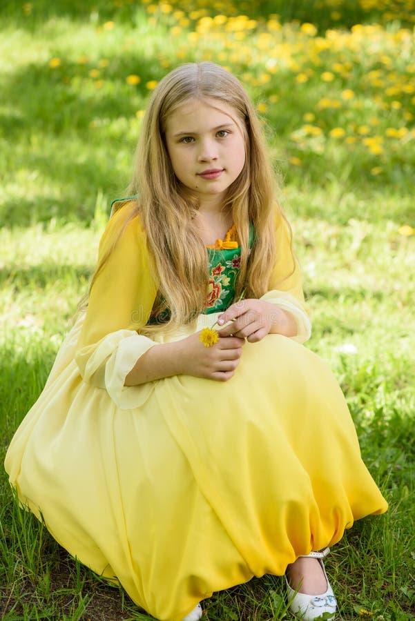 Blond ung flicka som poserar i en gul grön klänning som sitter på gräset med gula blommor för maskrosor royaltyfria bilder