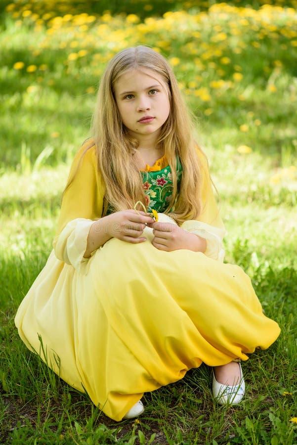 Blond ung flicka som poserar i en gul grön klänning som sitter på gräset med gula blommor för maskrosor royaltyfri foto