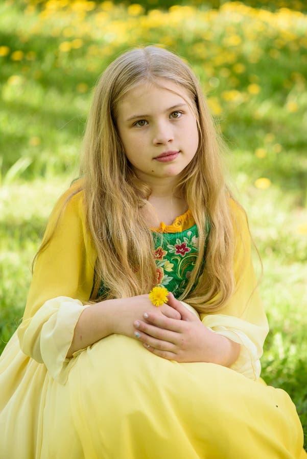 Blond ung flicka som poserar i en gul grön klänning som sitter på gräset med gula blommor för maskrosor arkivbilder