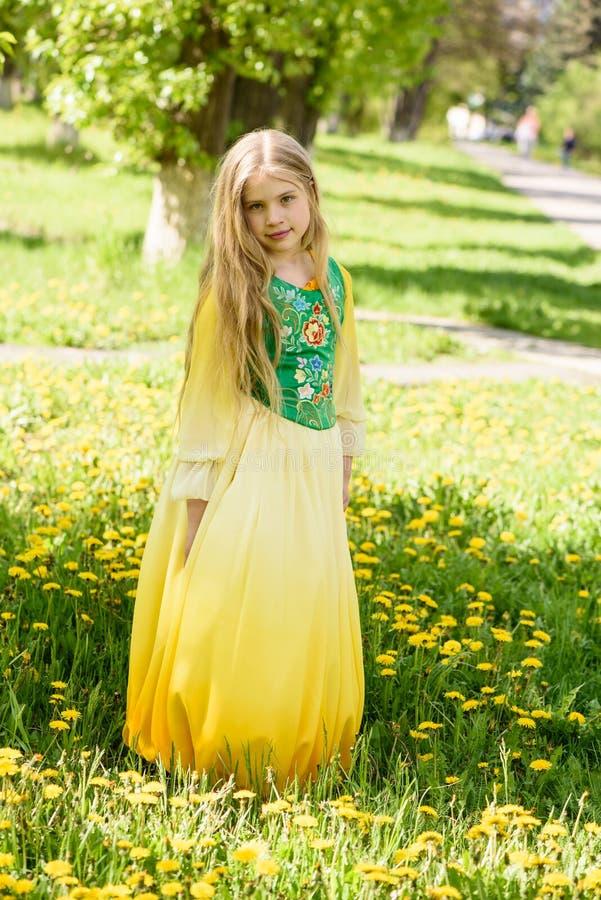 Blond ung flicka som poserar i ett gult grönt klänninganseende på gräset med gula blommor för maskrosor royaltyfria foton