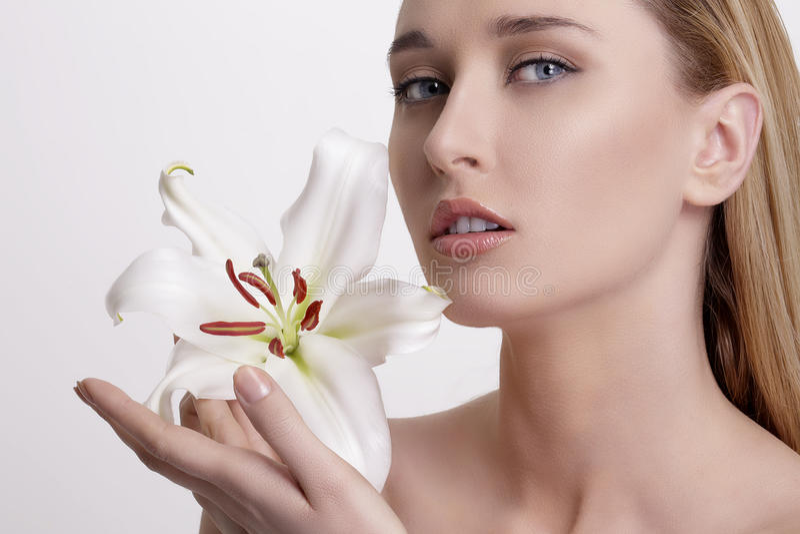 Blond ung kvinna för skönhet som visar en ny blomma royaltyfri bild