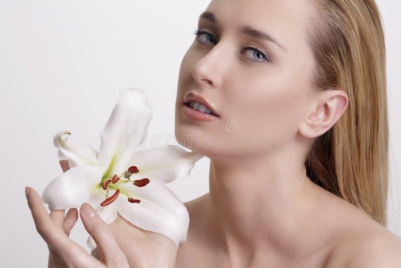 Blond ung kvinna för skönhet som visar en ny blomma arkivfoto