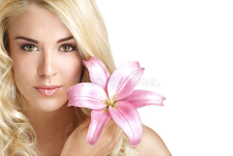 Blond ung kvinna för skönhet som visar en ny blomma på vit royaltyfri bild