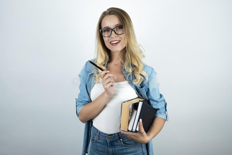 Blond ung kvinna i exponeringsglas som rymmer böcker och vit bakgrund för penna royaltyfri bild
