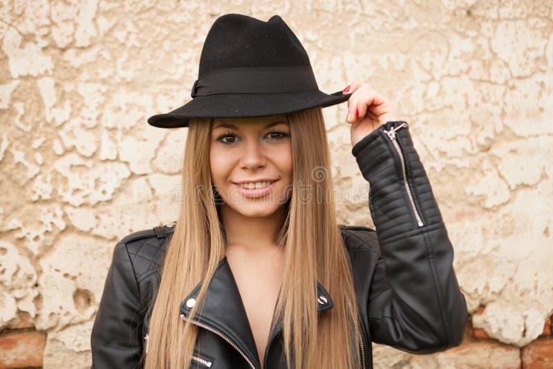 Blond ung kvinna med den svarta hatten arkivfoto