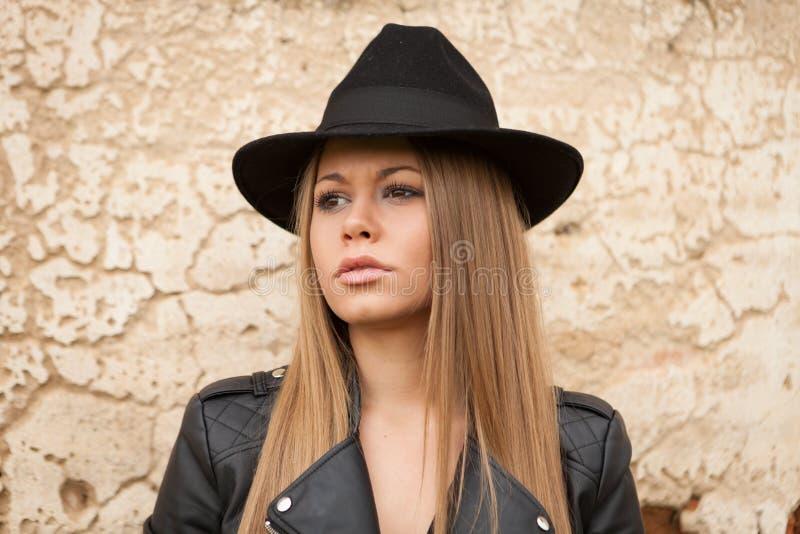 Blond ung kvinna med den svarta hatten royaltyfri bild