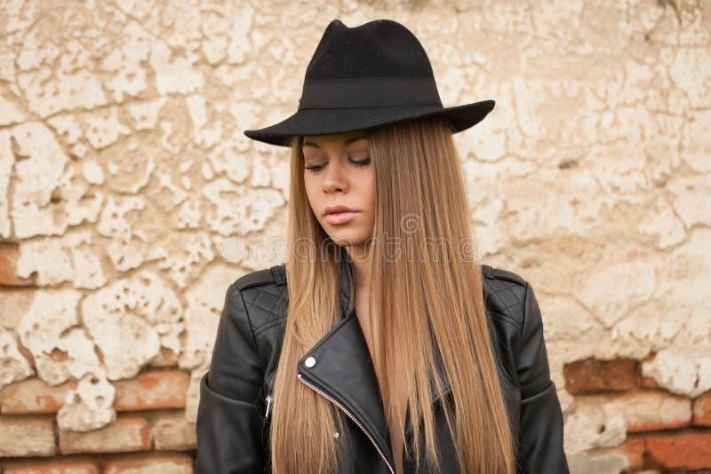 Blond ung kvinna med den svarta hatten arkivbilder