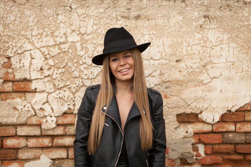 Blond ung kvinna med den svarta hatten som blinkar ett öga fotografering för bildbyråer