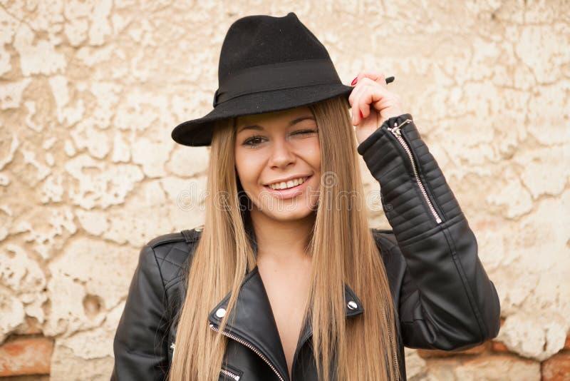 Blond ung kvinna med den svarta hatten som blinkar ett öga arkivbild