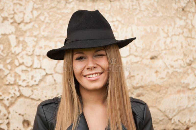 Blond ung kvinna med den svarta hatten som blinkar ett öga arkivfoto