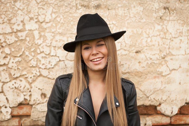 Blond ung kvinna med den svarta hatten som blinkar ett öga arkivfoton