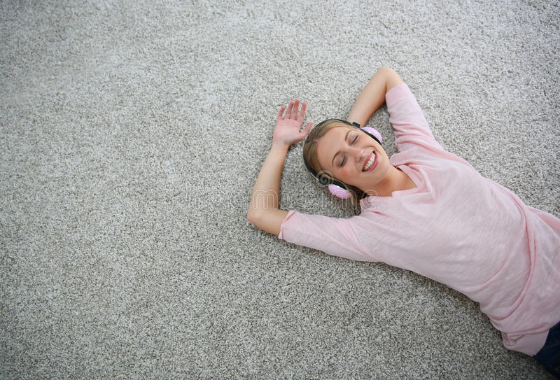 Blond ung kvinna som kopplar av på matta royaltyfri foto