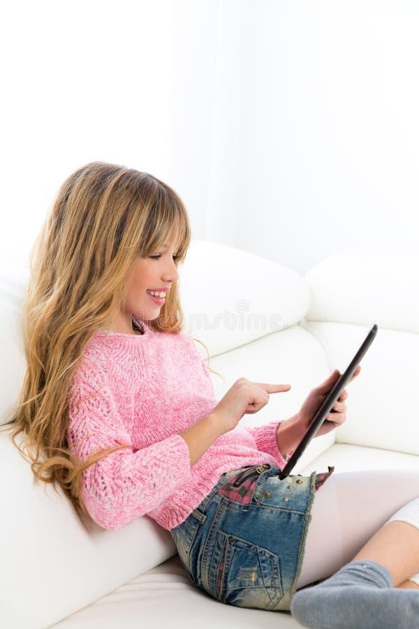 Blond ungeflicka som spelar med minnestavlaPC på den vita soffan royaltyfri fotografi