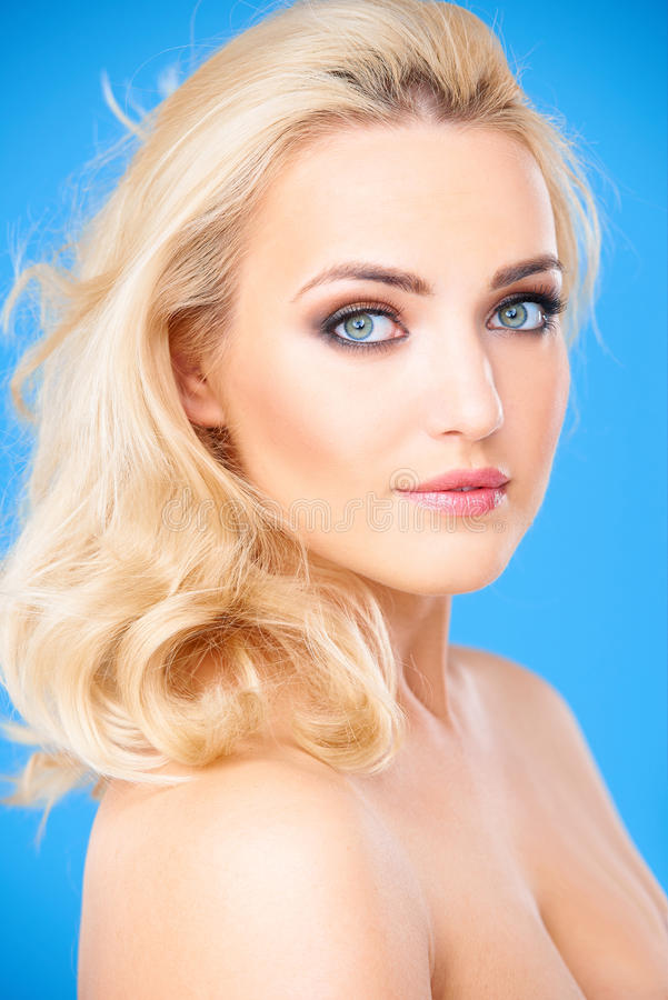 Blond vrouwelijk model die mooie make-up dragen stock foto